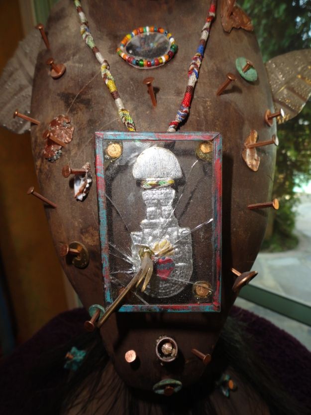 This detail symbolizes the shattering of the male side of the ego by a feminine consciousness. The gold object in the glass case is a small replica of the instrument used to sever the head in sacrificial prehispanic temple ceremonies. The hammer shattering the glass is meant to symbolize the gentling effect of the feminine on the msculine.