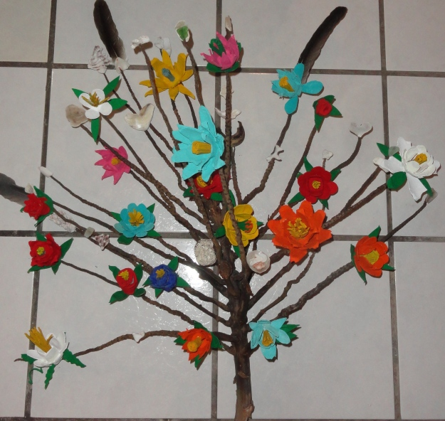 It started with a palm fruiting stem washed ashore.  I added flowers I made of cutouts from egg cartons, painted and glued together, then added pelican feathers and verious heart-shaped shells and small stones found on beach walks.
