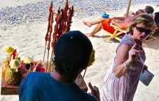 Centering the attention on the woman and beach vendor creates more tension. Is she ordering or scolding? The man in the background seems to be listening in as well.
