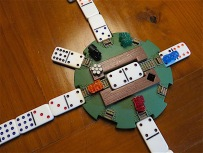 "Mexican Train offers an excellent opportunity to play with shapes. The round shape of the ""station"" is echoed by dots on the dominoes. The train tracks formed by the rectangular dominoes form semi-straight lines--all in all, a collage of rectangles and circles."