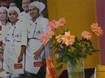 Fresh roses in front of a blowup from the cover of a magazine featuring students from a culinary institute who intern in Agustin's kitchen.