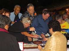 It just looks like these ladies are competing for the biggest piece. Actually, they were cutting the cake for everyone!