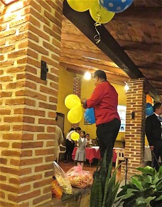 Agustin harvesting more balloons from the ceiling for the kids.