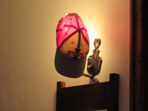 Ryan's hat drying out on the wall lamp after he was caught out in the rain during his big night out on the town.