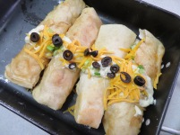 Fill pan with enchiladas and if you wish, put a narrow stream of sauce down the middle of enchiladas and top with scallions, grated cheddar and black olives.