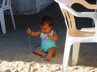 This adorable llittle miss snubbed the chairs in favor of the sand. The chair came in handy for pulling herself up into a standing position, though.